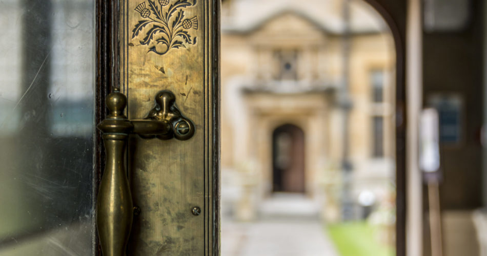Image of a decorative doorhandle, looking out to a qaud at the Examinations Schools, Oxford, a perfect filming venue in Oxford