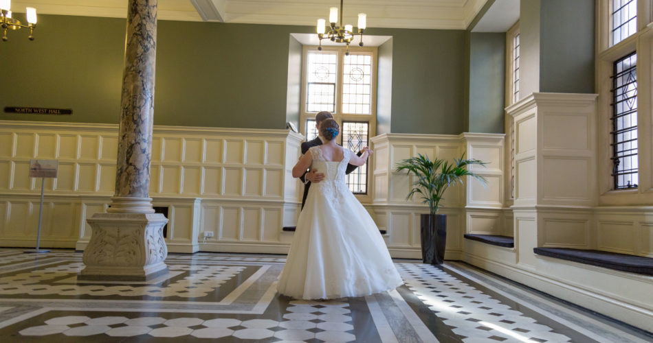 This is an image of a bride and groom dancing in the foyer area of the Examination Schools
