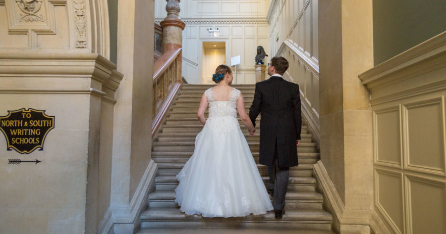 This is an image of a bride and groom going up the marble staircase at the Examination Schools
