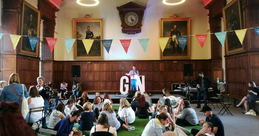 This is an image of people relaxing at a Gin festival in the South Schools room at the Examination Schools