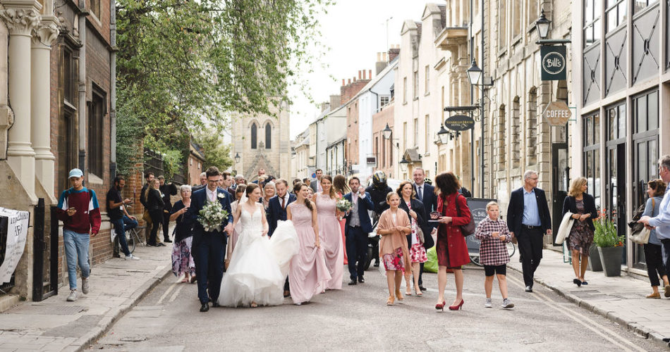 Bride and groom walk through streets of Oxford
