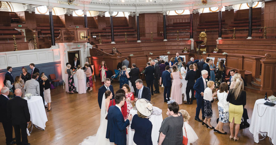 Bride and groom greeting guests in the Sheldonian Theatre