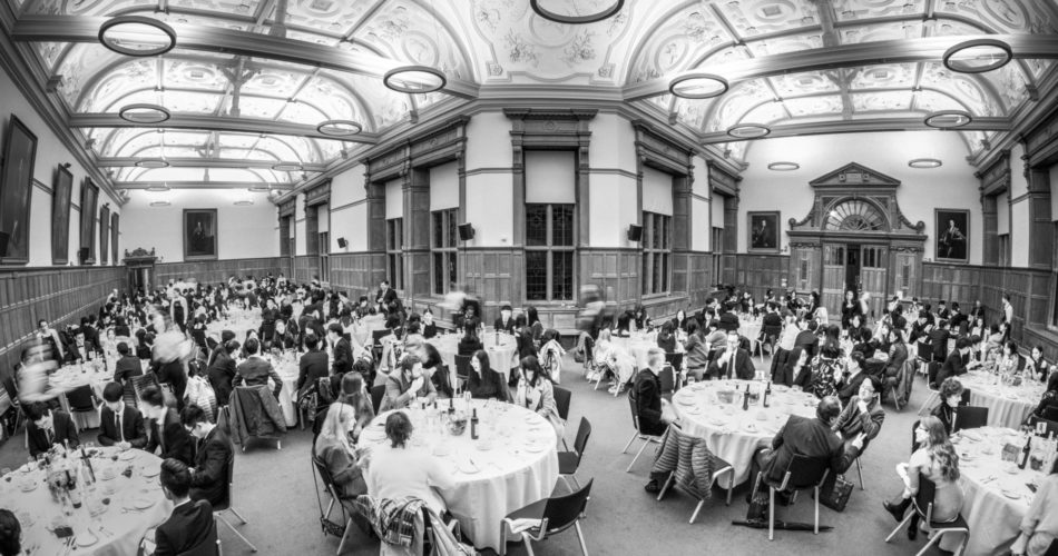 This is a black and white image of guests sat at tables attending a dinner in the North Schools at the Examination Schools