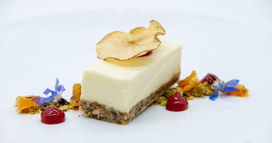 This image shows a cheesecake with fruit couli and is an example of the desserts we can supply