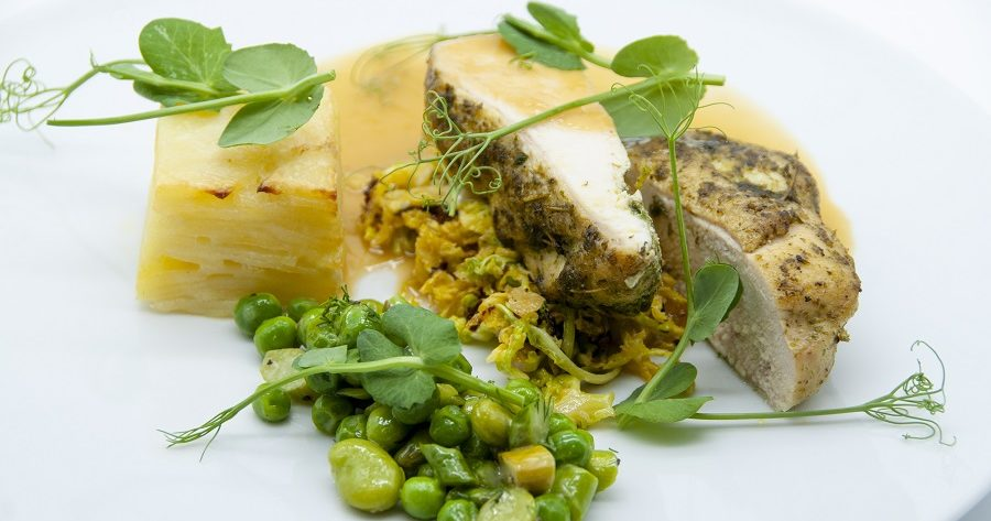 This image shows chicken and potato rosti with pea and salad